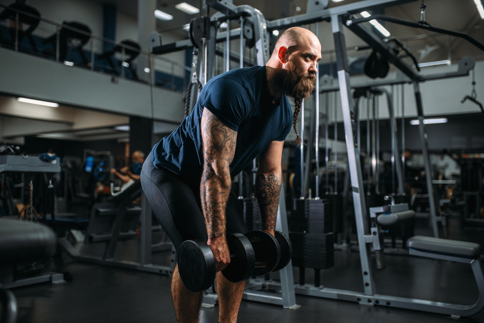 strong athlete with dumbbells training in gym