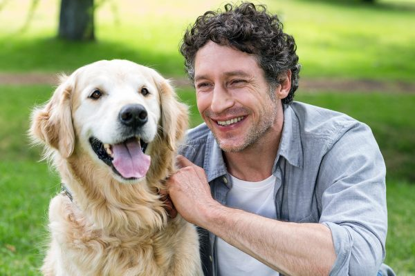smiling man with his dog in park on a sunny day PDNWL2X