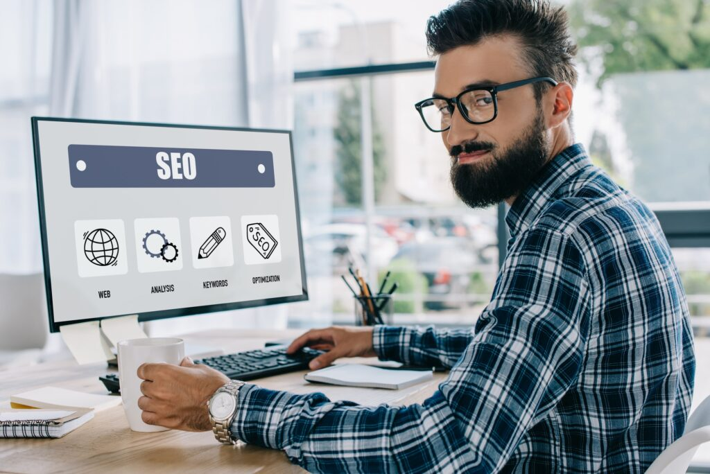 young successful seo manager sitting at workplace with computer and looking at camera